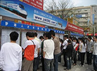 Job seekers scan the recruitment ads outside Shenzhen's Luohu Talent Market